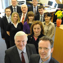 Pictured front: BCS' founder and partner, Patrick O'Farrell (left) with son and new managing partner David O'Farrell (right), and Louise O'Farrell - nee Barrell – BCS partner (front centre). Second row from front (left to right): BCS employees - Melanie Johnson, Samantha Thomas and Rosie Smith. Third row (left to right): BCS employee Ryan Burkett, entrepreneur Alan Barrell and BCS employee Adam Laker. Back row (left to right): Stephen Dockerty (IFA) and David Wood (BCS Recruitment Consultant to BC