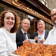 (From left to right): New tenant Alison Wright: Simon Lewis, director of Cheffins: Chris Blencowe, Bursar of Pembroke College: and Tim Hayward – Alison's husband – with a tray of the famous Chelsea buns.